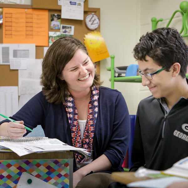 female teacher smiles while helping young male student with schoolwork